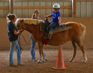 Young man riding a horse through Springbrook's Therapeutic Horse Program