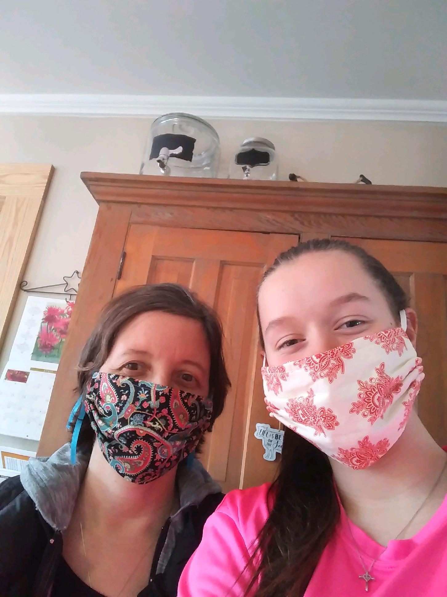 Meg Shivers and her daughter demonstrate the masks they created for Springbrook